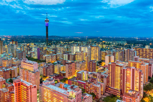 Johannesburg cityscape in the evening dusk across Hillbrow residential suburb of towering apartments. The iconic Hillbrow communication tower seen in the midst. Johannesburg is one of the forty largest metropolitan cities in the world, and the world's largest city that is not situated on a river, lakeside, or coastline. It is also the source of a large-scale gold and diamond trade, due being situated in the mineral-rich Gauteng province.
