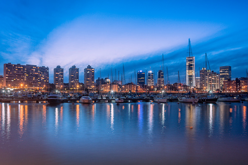 Skyline of Montevideo from Puerto del Buceo at dusk. Finance and business buildings as well as luxury residential towers. Building lights reflections on water.